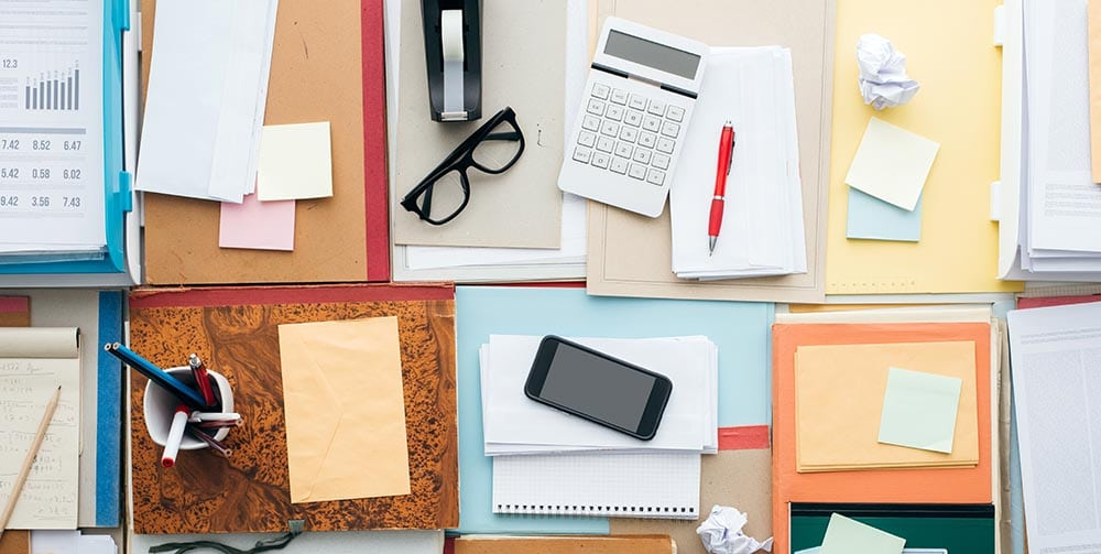 Full business desktop with piles of paperwork and objects, business productivity and work organization concept