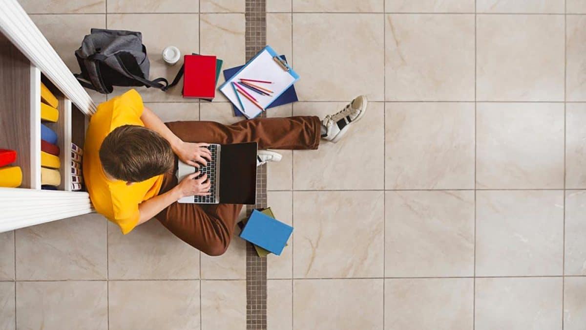 Zarządzenie Dziekana ws. przedłużenia sesji egzaminacyjnej young male student sitting at bookshelf and using TP38BUY 1200x675