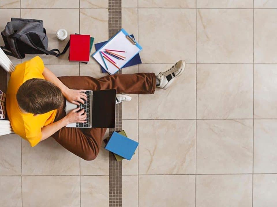 Zarządzenie Dziekana ws. przedłużenia sesji egzaminacyjnej young male student sitting at bookshelf and using TP38BUY 960x720
