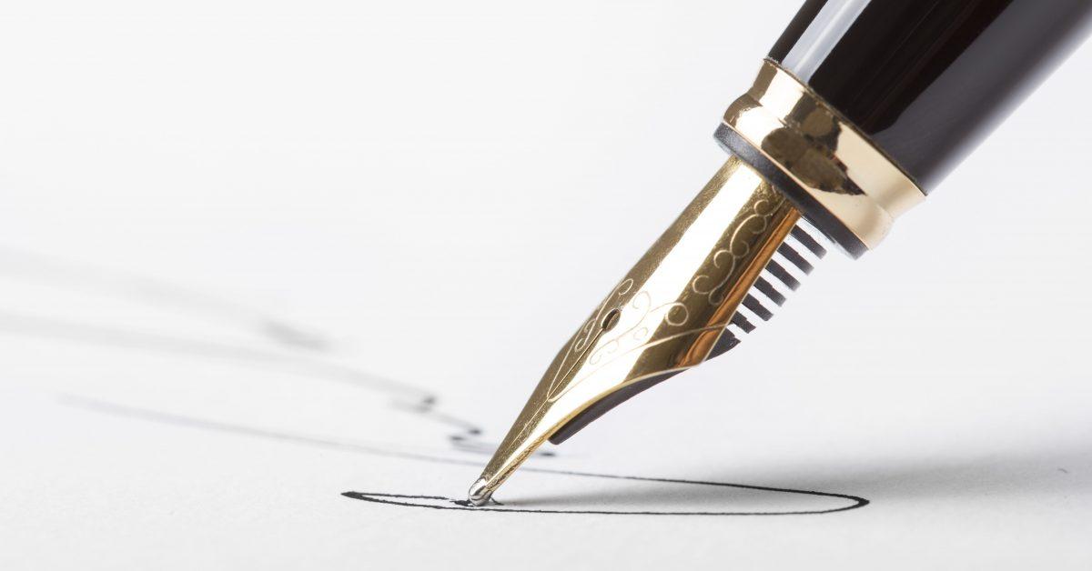 pen signing white paper