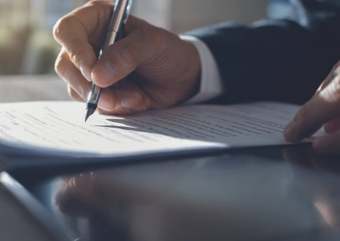 Business man in black suit signing contract document with ldigital tablet on office desk, deal concept, close up