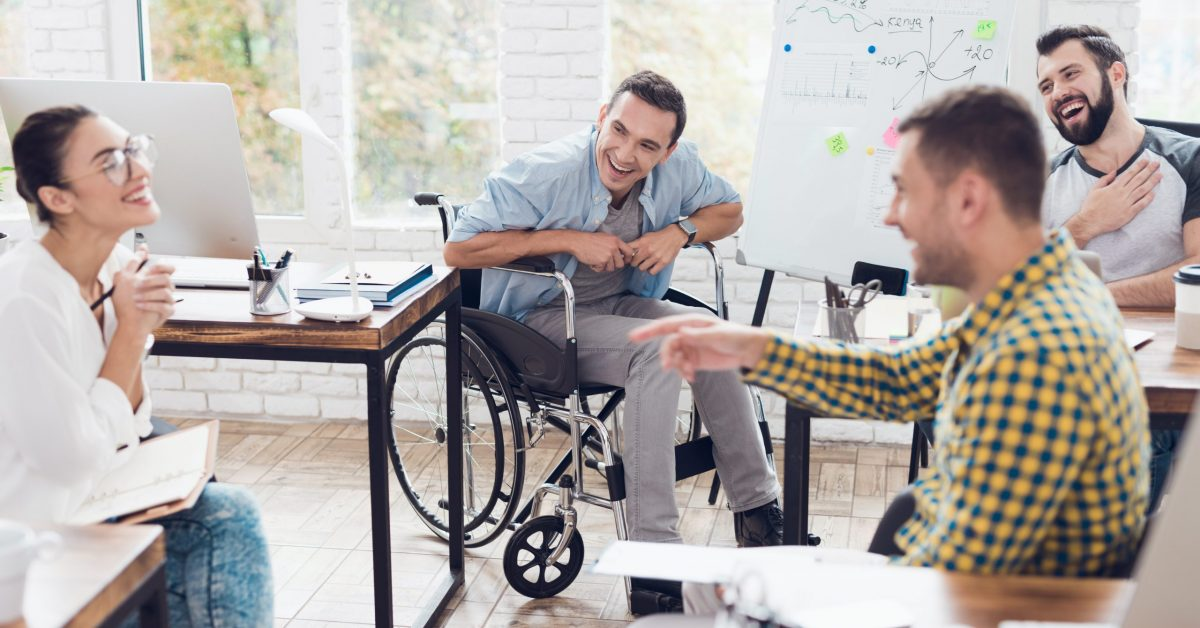 A man in a wheelchair demonstrates business graphics. He is holding a green marker. Collegues are listening attentively to him and laughing.